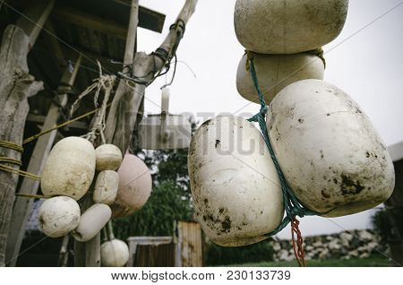 Close Up And Selective Focus Group Of White Buoy Tied With Rope, Hanging Under Wooden Cottage Over B
