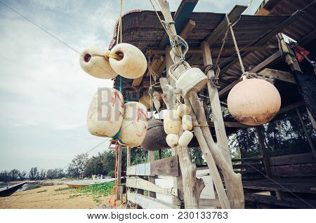 Selective Focus Group Of White Buoy Tied With Rope, Hanging Under Wooden Cottage Over Blurred Backgr