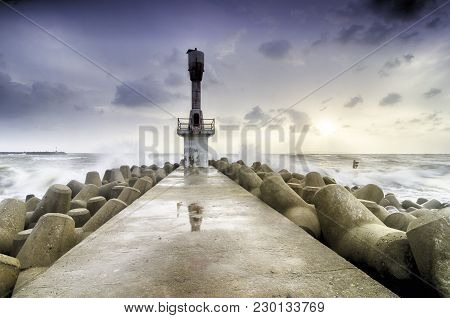 Abandon Beacon Light Tower With Concrete Break Water Surrounded By Sea Water And Blur Sunrise Backgr