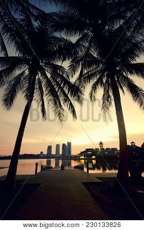 Blurred Silhouette Image At The Lakeside During Sunrise. Coconut Tree, Building And The Reflection O