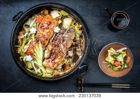Japanese chan chan yaki hot pot with salmon fillet as top view in traditional cast iron pot