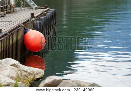 Pier With Red Buoy Ball, Norway Fjord Water In Background. Idyllic Scandinavia