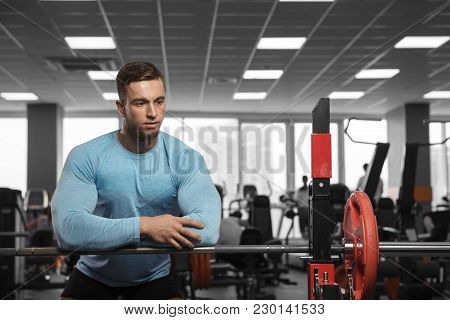 A Handsome Male Bodybuilder Is Resting After Exercising In The Gym Next To The Barbell.