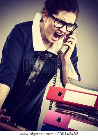 Mobbing At Work, Bad Job Relations Concept. Angry Mad Bossy Businesswoman Talking On Phone Sitting W