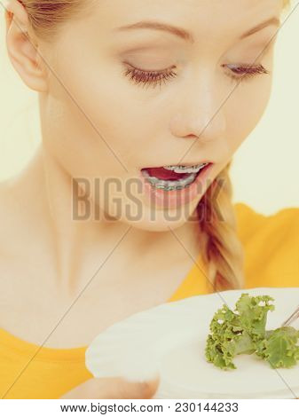 Shocked Young Blonde Woman Dealing With Anorexia Nervosa Or Builimia Having Small Green Vegetable On