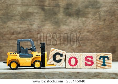 Yellow Toy Forklift Hold Letter Block C To Complete Word Cost On Wood Background