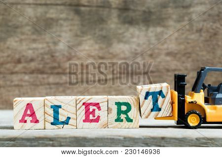 Yellow Toy Forklift Hold Letter Block T To Complete Word Alert On Wood Background