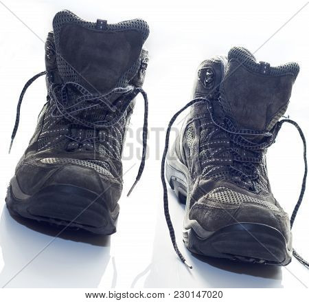 Hiking Boots On White Counter Top After Long Day Of Walking. Laces Undone. Walking Boots At An Angle
