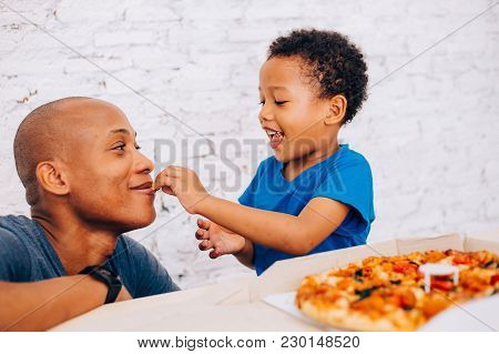 Cute Little African American Child Feeding His Father With Pizza. Warm Family, Father And Son Relati