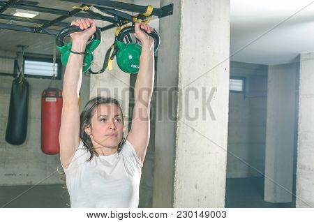 Pretty And Handsome Girl Holding Two Kettlebells In Her Hands For Strength And Conditioning Fitness