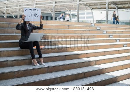 Business Woman Unemployed From Company Sitting On The Staircase And Holding Poster With Text Is Look