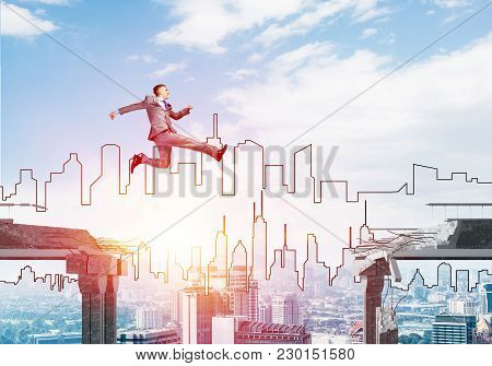 Businessman Jumping Over Gap In Concrete Bridge As Symbol Of Overcoming Challenges. Sunlight And Cit