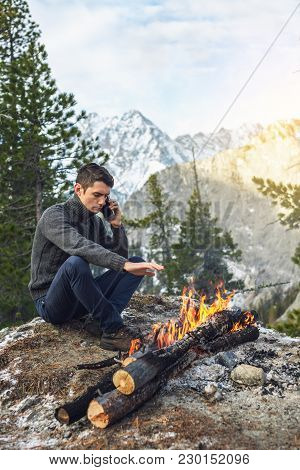 Man Sits On The Nature Of The Campfire Talking On The Phone. Concept Of Mobile Communication, Hiking