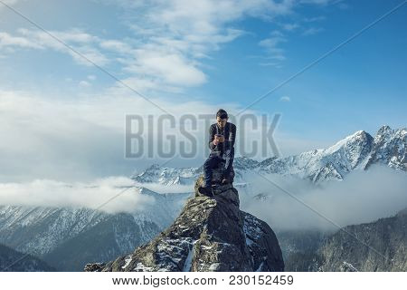 Young Man In A Sweater With Phone In Hand On The Top Of A Snowy Mountain. Concept Availability Of Mo