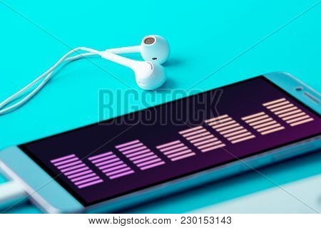 Phone With White Earphones On Blue Background. Concept Of Modern Music And Technology