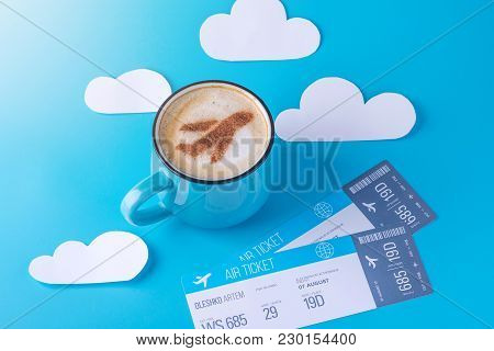 Cup Of Cappuccino With A Picture Of The Plane On The Foam And Tickets. Blue Sky Background With Pape