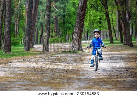 Happy Cute Blond Kid Boy Having Fun His First Bike On Sunny Summer Day, Outdoors. Happy Child Making