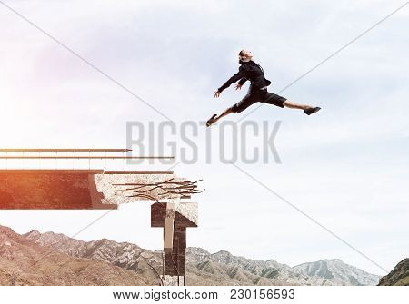 Business Woman Jumping Over Huge Gap In Concrete Bridge As Symbol Of Overcoming Challenges. Skyscape