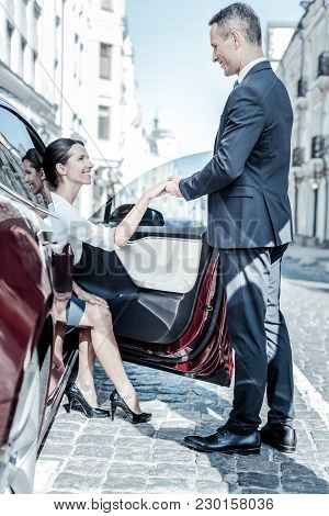 Polite Manners. Nice Young Happy Woman Looking At Her Colleague And Holding His Hand While Getting O