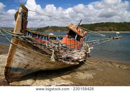 Old Broken Fishing Boat Wrecked Against The River