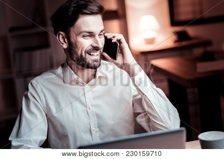 Hey Its Me. Satisfied Pleasant Stylish Man Sitting In The Office Having Phone Conversation And Smili