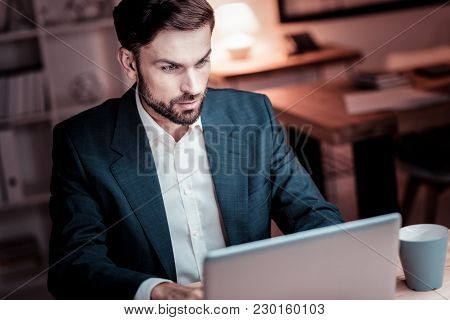 Full Concentration. Serious Occupied Interested Man Sitting In The Office And Using The Laptop Focus