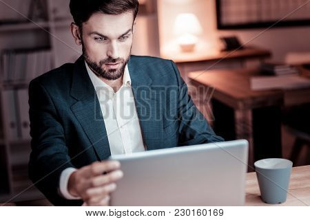 New Details. Busy Stylish Responsible Worker Sitting By The Table Using Laptop Touching To The Scree