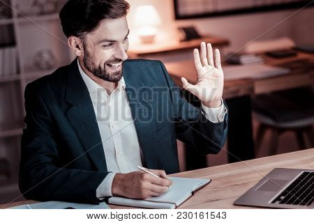 Nice To Meet You. Satisfied Occupied Stylish Man Sitting By His Desktop Having Video Conversation An