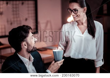 Take It Please. Bespectacled Satisfied Cute Woman Standing In The Cabinet Smiling And Bringing Tea F