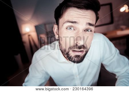 Whats Wrong. Interested Disappointed Unshaken Man Spending Time In The Specious Room Looking Straigh
