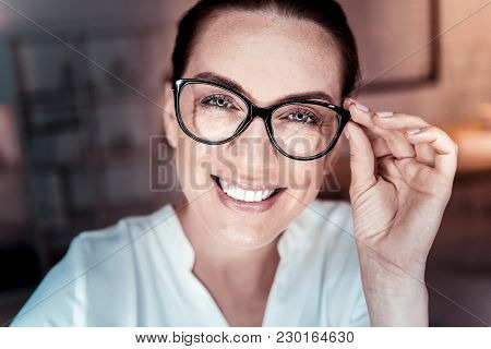 Good Joke. Satisfied Pleasant Bespectacled Woman Looking Straight Supporting Her Glasses And Smiling