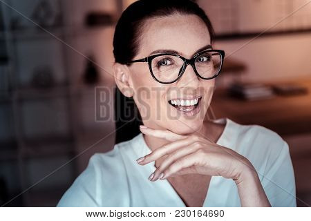 Tell Me Something. Joyful Pretty Bespectacled Woman Being In The Empty Room Smiling And Holding Head