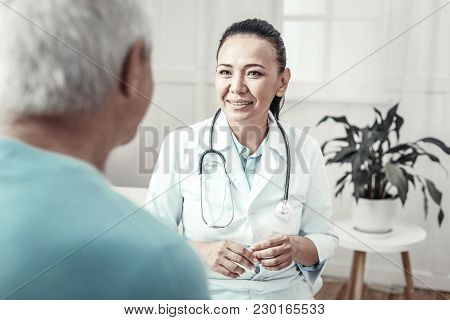 Best Doctor. Skilled Cute Mature Nurse Sitting In The Room Near A Man Smiling And Having Consultatio