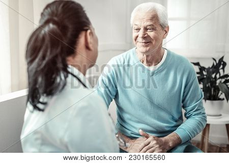 Consulting Conversation. Senior Gray Hair Pleasant Man Sitting In The Room And Looking At The Doctor