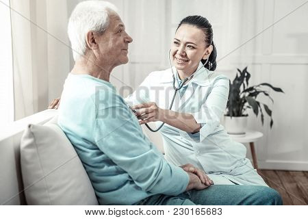 Useful Utensil. Pleasant Kind Cute Nurse Sitting In The Room Near A Man Using Her Stethoscope And Sm