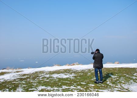 Photographer Shooting By A Coast With Melting Snow By Spring Season