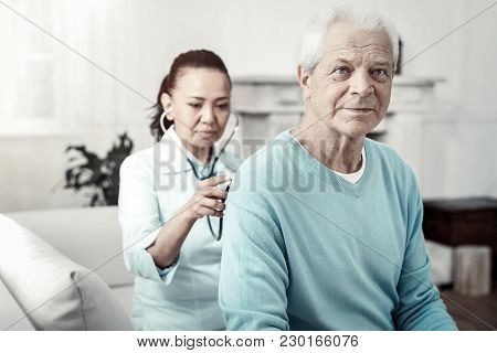 Relax And Breathe. Aged Pleasant Concentrated Man Sitting In The Room On The Sofa Doing Nurses Order