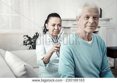 Skilled Nurse. Cute Serious Reliable Nurse Sitting In The Room Behind The Man Listening To The Patie