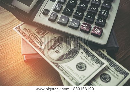 Calculator Notebook And 100 Dollar Bill On Wooden Desk