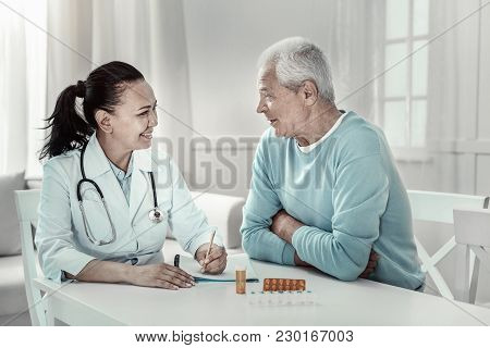 Medical Advice. Pleasant Kind Mature Nurse Sitting In The Bright Room By The Table Having Conversati