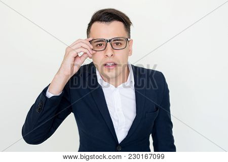 Closeup Portrait Of Focused Handsome Young Man Staring At Camera Through Glasses. Interest Concept.