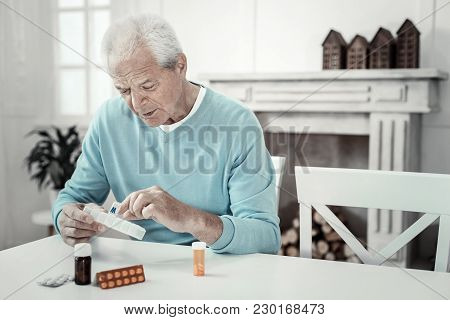 Helpful Medicine. Aged Interested Serious Man Sitting In The Room By The Table Holding Pack Of Table