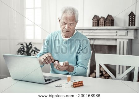 Prescription Medicine. Serious Concentrated Senior Man Sitting By The Table Near The Laptop Taking T