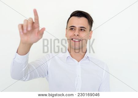 Closeup Portrait Of Smiling Young Handsome Man Touching Invisible Screen With His Forefinger. Soluti