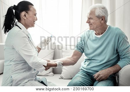 Im Not Afraid. Joyful Cute Pleasant Nurse Sitting Near Her Patient Smiling And Making Injection For