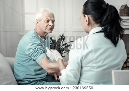 Special Procedure. Pleasant Senior Man Sitting In The Room Near The Doctor Preparing His Arm For Inj