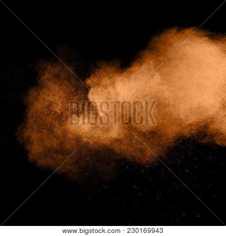 Abstract Orange Dust Explosion On  Black Background. Abstract Orange Powder Splattered On Dark Backg