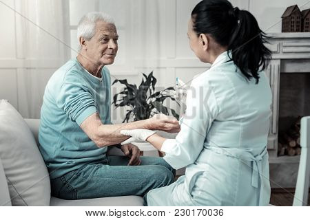 Trust Me. Pleasant Kind Aged Man Sitting On The Sofa Looking At The Doctor And Giving Her His Arm Fo