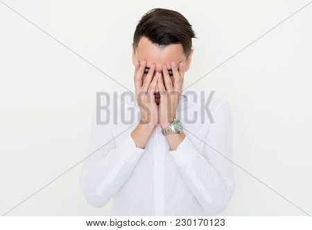 Closeup Of Young Man Covering Face With Hands. Depression Concept. Isolated Front View On White Back