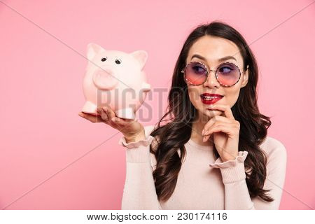 Image of fascinating woman 20s with long dark hair in girlish glasses holding piggybank on palm isolated over pink background